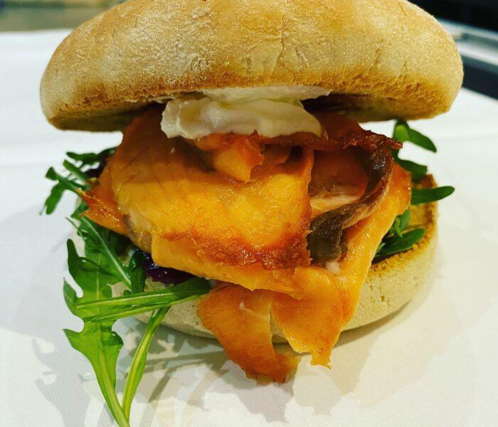 """Lachs-Burger """"Stockholm"""" serviert auf einem Burgerbrötchen mit Rucola, Getrüffeltem Rotkraut und Schmand"""